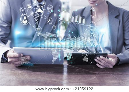 Technology interface against business people discussing over tablet pcs
