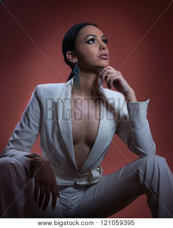 Young beautiful brunette woman in elegant white suit with trousers sitting. Seductive dark hair girl
