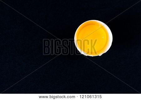 Broken egg on a black background