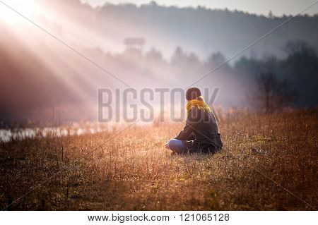 Young Woman Sitting On Grass On Meadow