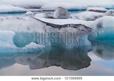 Abstract image of a few luminous Blue Icebergs, with black lines, Floating In Jökulsárlón Glacial Lagoon, Iceland
