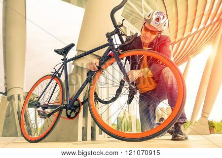 Business man locking bicycle with metal chain outside urban building bike parking - Guy fasten padlock at wheel sport cycle outdoor - Focus on left hand with nostalgic vintage filter and sun flare poster
