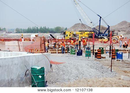 multi-cultural crew pour concrete on industrial construction site