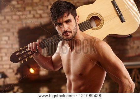 Sexy young man holding guitar on shoulder, bare chest.