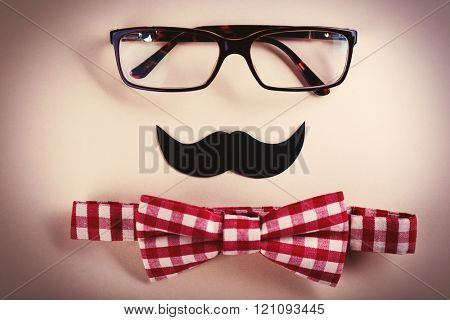Bow tie, glasses, mustache on beige background