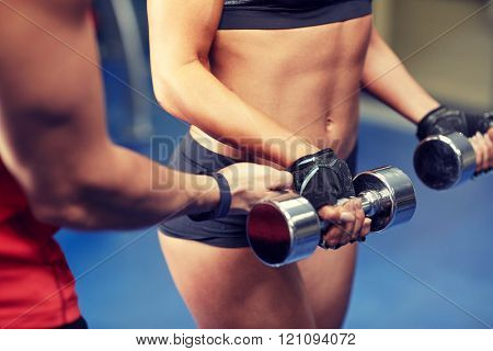 fitness, sport, bodybuilding and weightlifting concept - close up of young woman and personal trainer with dumbbells flexing muscles in gym poster