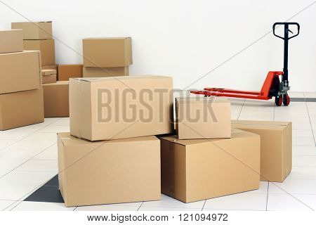 Stack of carton boxes and manual pallet truck indoors