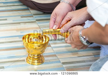 Couple hands holding Buddhist's grail pouring water