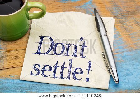 Do not settle reminder - handwriting on a napkin with a cup of coffee