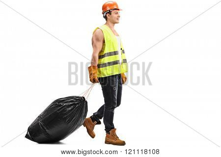 Full length profile shot of a young waste collector dragging a black bag of trash isolated on white background