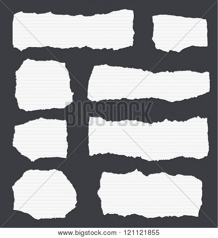 Pieces of torn white lined note paper on black background