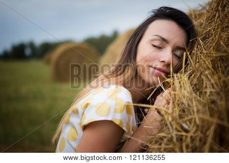 girl with eyes closed leaning against the hayloft