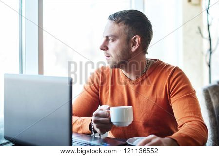 Handsome Young Man Working On Notebook, Thinking, Looking Out The Window, While Enjoying Coffee In C