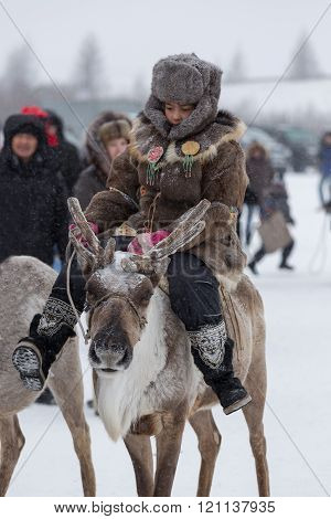 The Evenk Girl  Riding A Reindeer