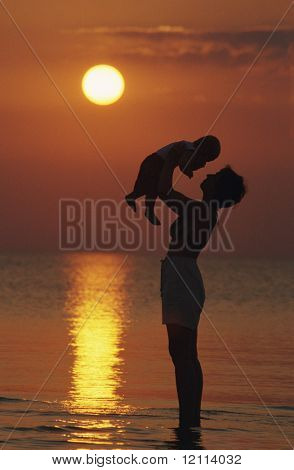 mother and baby at beach sunset
