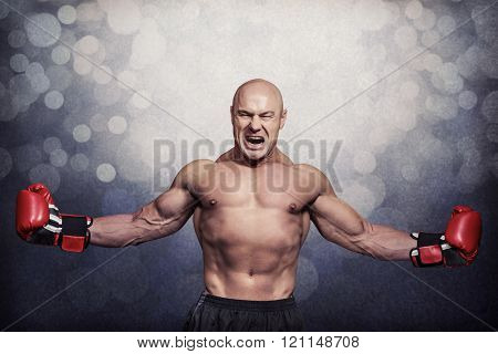 Successful boxer with arms outstretched against grey