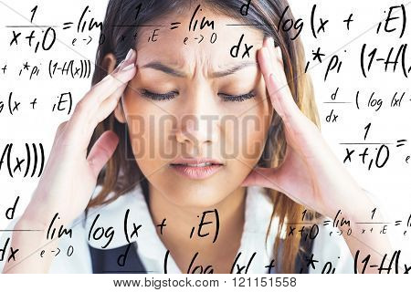 Nervous businesswoman holding her head against maths equation