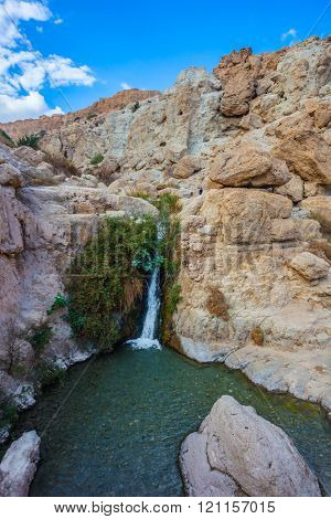 Adorable little waterfall among rocks parched desert. The journey through the national park Ein Gedi, Israel