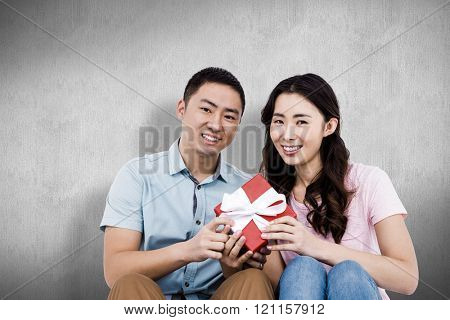 Happy couple holding gift box against white and grey background
