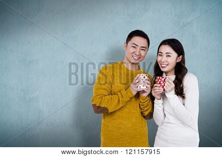 Portrait of happy young couple holding cups against blue background