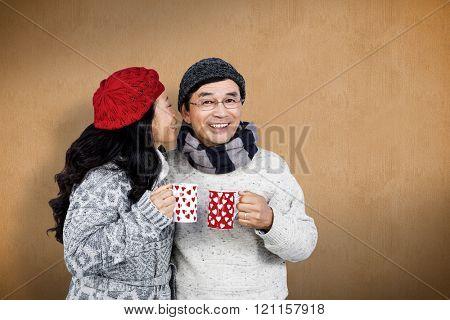Older asian couple having hot drinks against orange background
