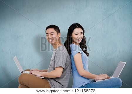 Portrait of young happy couple using laptop while sitting against blue background