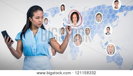 Serious businesswoman with calculator writing with pen against background with world map
