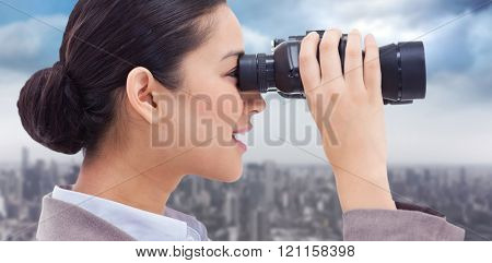 Side view of a businesswoman looking through binoculars against cityscape