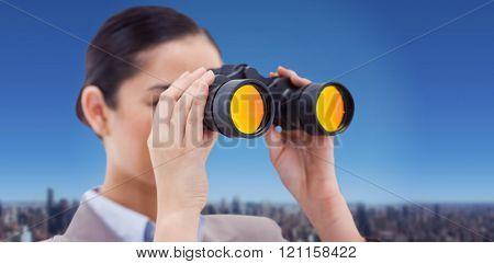 Brunette businesswoman looking through binoculars against cityscape