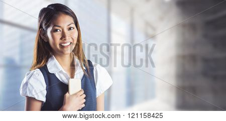 Smiling businesswoman holding a smartphone against modern room overlooking city