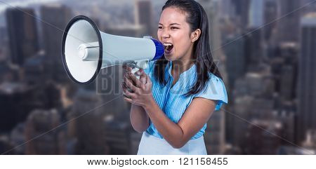 Businesswoman shouting into a megaphone against view of cityscape