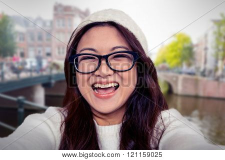 Asian woman smiling at the camera against canal in amsterdam