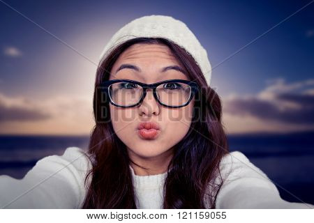 Asian woman making faces against scenic view of sea against sky