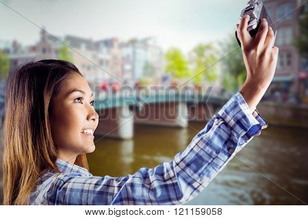 Smiling asian woman taking picture with camera against canal in amsterdam