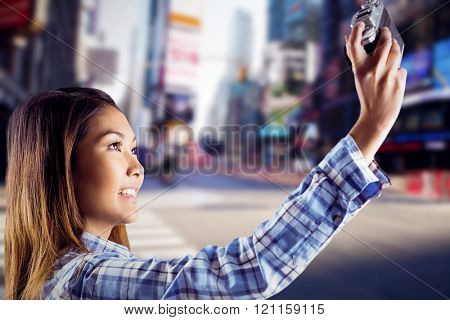 Smiling asian woman taking picture with camera against blurry new york street