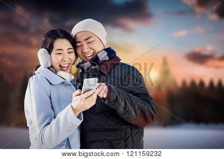 Cheerful couple looking at the smart phone against fir tree forest in snowy landscape