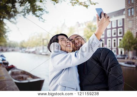 Cute couple taking selfie against canal in amsterdam