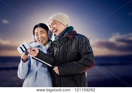 Couple laughing at their pictures taken on smartphone against scenic view of sea against sky