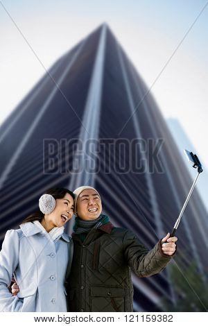 Couples taking funny pictures using smartphone against skyscraper