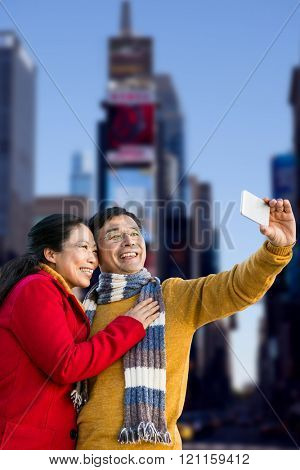 Older asian couple on balcony taking selfie against view of building