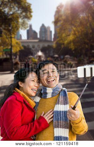 Older asian couple on balcony taking selfie against new york street