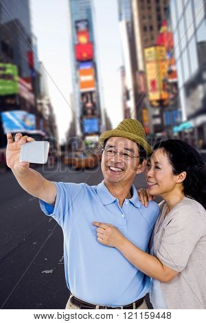 Man and woman taking a picture against picture of a city