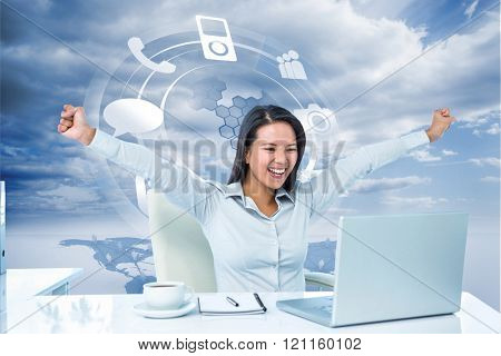 Happy businesswoman with raised arms against hologram with smartphone icons standing over a planet