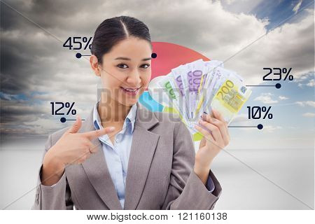 Smiling businesswoman holding bank notes against view of graph with percentage