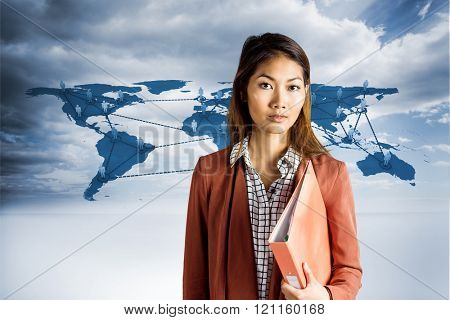 Businesswoman holding a binder against view of a global map
