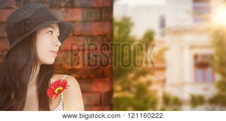 Cheerful woman with flower looking away wearing a hat against wall of a house