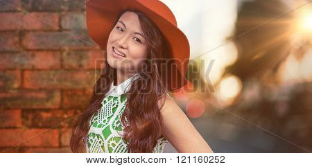 Asian woman with hat posing for camera against wall of a house