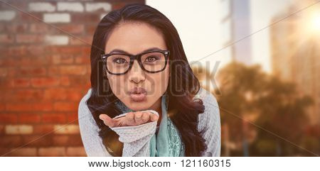 Asian woman blowing kiss to the camera against wall of a house