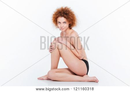 Beautiful naked woman with curly hair sitting on the floor isolated on a white background