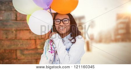 Asian woman holding colorful balloons against wall of a house